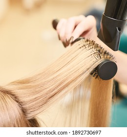 Repair long hair procedure. Haircut at salon. Woman hairstyle. Master hand with brush and fan. Adult female person. Closeup view. Studio equipment. Lady preparation. Blonde dry.