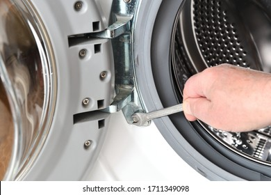 Repair and maintenance of the washing machine. The worker unscrews the door of the washing machine using a key.