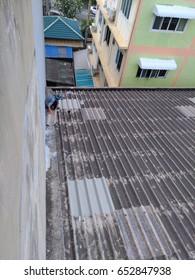 Repair man on old roof