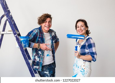 Repair, renovation and love couple concept - young family doing repair and painting walls together and laughing