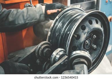 Repair and restoration of car wheel drive by mechanic master on professional machine equipment tool in car repair garage service, close up