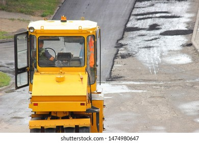 Repair of the road, steamroller laying new asphalt, industrial machinery - big yellow asphalt roller on summer dayon construction site
