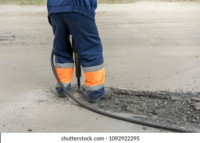 repair of roads. the worker is repairing the road. The man is working with a jackhammer.