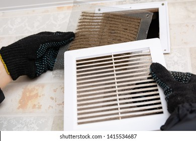 repair service man removing a dirty air filter on a house so he can replace it with a new clean. Extremely dirty and dusty white plastic ventilation air grille at home close up, harmful for health
