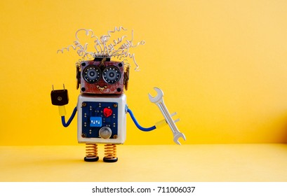 Repair service robot handyman hand wrench. Creative design cyborg toy, electric wires hairstyle, big eye glasses, electronic circuit body, red heart. yellow background. copy space