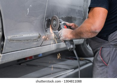 Repair service worker fix damaged car. Working with angle grinder to fix metal body