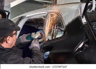 Repair service worker fix damaged car. Working with angle grinder to fix metal body.