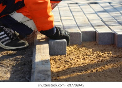 Repair of the sidewalk. Worker stonemason repair the sidewalk for Laying paving slab
