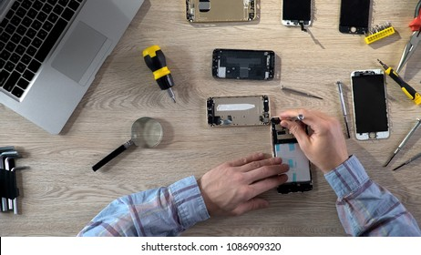 Repair specialists upgrading and maintaining gadgets, examining broken phones