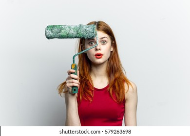 repair woman with a roller for painting walls