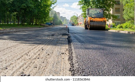 Repair works on laying the asphalt surface on a city street. Steamroller machine for laying asphalt