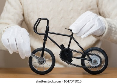 Repairing an antique miniature bicycle.