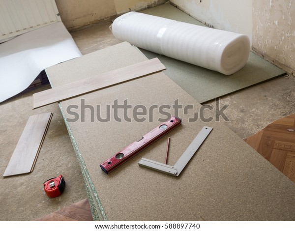 Repairing apartment's  floor . Plates of pressed wood chips. Laminate. Measuring the Tools, building level, tape measure.