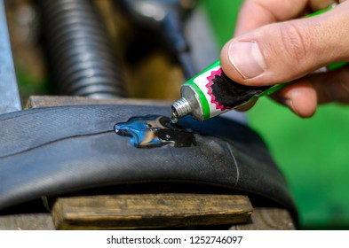Repairing bicycle tube In workshop. Close up image of glue to repair inner tube of bicycle wheel. The mechanic does his job thoroughly.