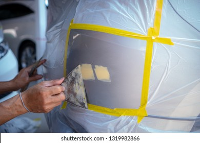 Repairing car body by puttying close up work after the accident by working sanding primer before painting. , The mechanic repair the car  , Using plastic putty ,Prepare surface for spray painting