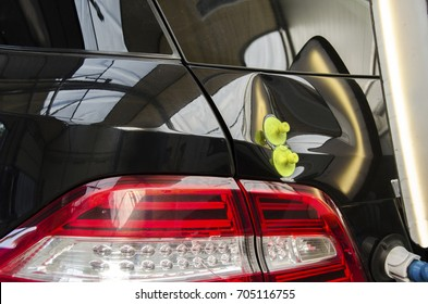 Repairing car dent after the accident by paintless dent repair.