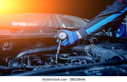 Repairing engine at service station. Engine compression measurement. Car repair. Background