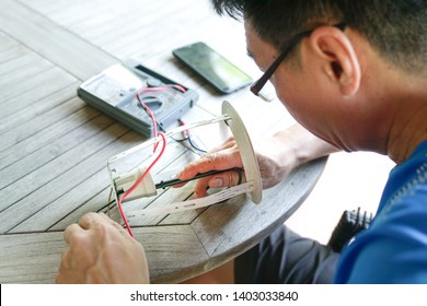Repairing and fixing light bulb by checking voltage at the electrical terminal of the light lamp wiht a multimedia. A maintenance or home improvement concept.