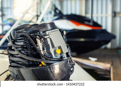 Repairing inflatable motorboat engine at boat garage. Ship engine seasonal service and maintenance. Vessel motor with open cover