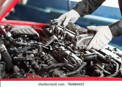 Repairing of modern diesel engine, workers hands and tool. Car mechanic looking at engine for analysis symptoms of car at maintenance repair service station