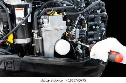 Repairing  outboard marine engine. Motorboat engine seasonal service and maintenance. Mechanic hand performing maintenance on outboard engine