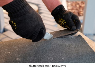Repairing of roof by cutting felt for installing bitumen shingles during waterproofing works.