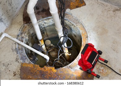 Repairing a sump pump in a basement with a red LED light illuminating the pit and pipe work for draining ground water