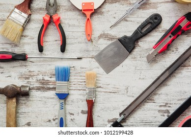 Repairing tool kit on grey wooden background with screwdriver, hammer, saw, pliers, brush, spatula, cutter and paint tape.