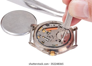 Repairing of watch - watchmaker replaces battery in quartz wristwatch isolated on white background