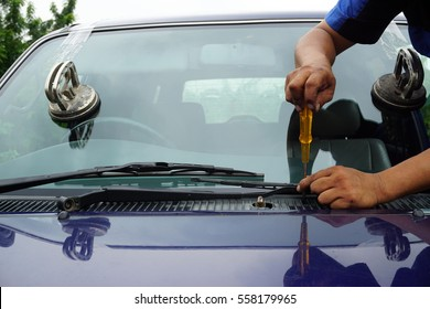repairing windshield replace windscreen wiper tools fix crack broken front window glass car vehicle services by Glazier. Maintenance repair, replace windshield, windscreen car wiper concept.