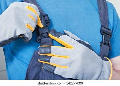 Repairman adjusting his working overalls