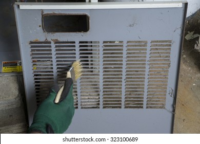 Repairman   cleaning the front cover of a gas furnace before re-installing .