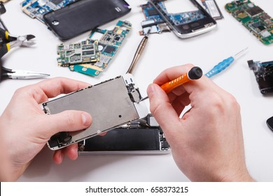 Repairman disassembling smartphone with screwdriver. Technician fixing broken phone, electronics repair service, repairer pov
