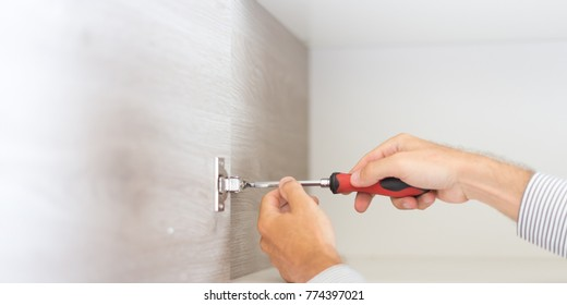 Repairman fixing a brand new kitchen, construction and architecture concepts