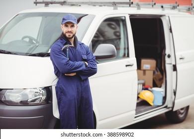 Repairman holding a hammer in front of his van