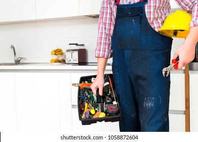 Repairman holding open toolbox in the kitchen