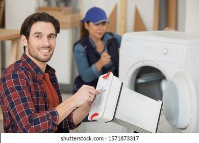 repairman holding tumble dryer condenser