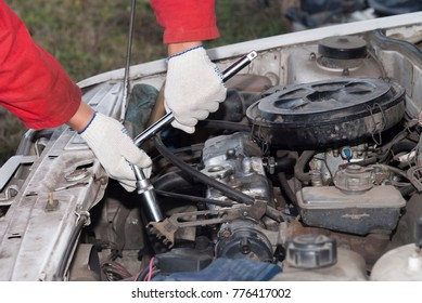 repairman holding a wrench on the background of a car