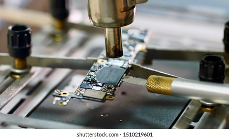 Repairman inserts knife under chip's part heating it with dryer. Removing chipset element microprocessor using knife melted with soldering dryer. Electronics engineer repairing chip in workshop.