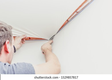 Repairman installing stretch ceiling with a special tool in the room.