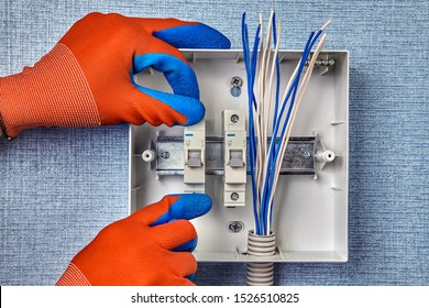 The repairman installs a new electrical panel with automatic fuses for the household electric network. Installation of the switchboard in the home electricity system, install the fuse box.