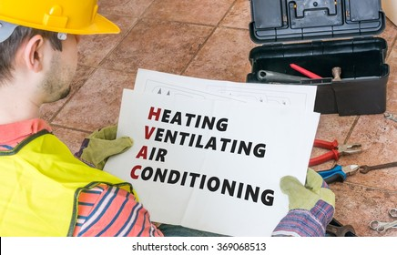 Repairman is looking at documentation of HVAC (Heating, Ventilating, Air Conditioning).