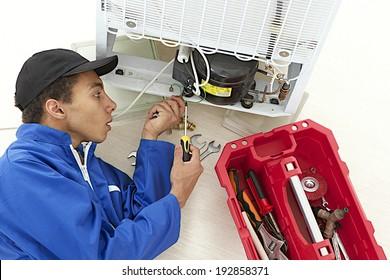 Repairman makes refrigerator appliance maintenance works