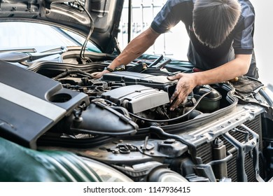 repairman or mechanic during car repair investigate cause of problem (mechanism or combustion system check) automobile gasoline or diesel engine at garage