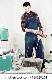 Repairman mixing dry mortar with handheld mixer in bucket