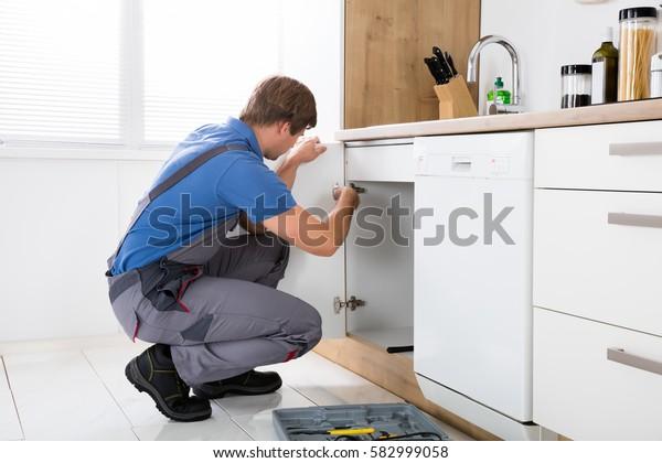 Reparateur in Overalls Reparatur Kabinettschacht in Küche