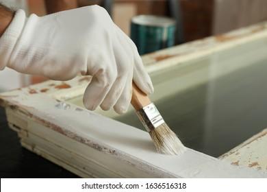 Repairman painting old window at table indoors, closeup