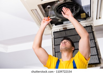 Repairman repairing ceiling air conditioning unit