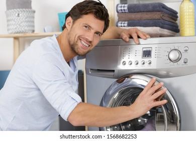repairman repairing washing machine in the kitchen
