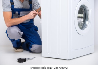 Repairman is repairing a washing machine on the white background.